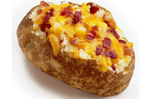 Gepofte aardappel in de schil, geserveerd met krokant gebakken spekjes, zure room en geraspte kaas