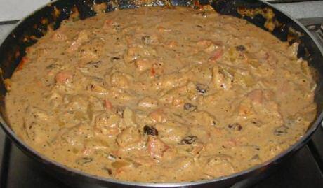 Kip curry saus waar daarna de gekookte rijst wordt geroerd om op te warmen en direct te serveren