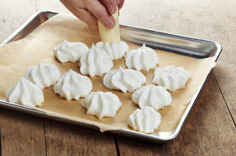 Meringue spuiten met een spuitzak op boterpapier