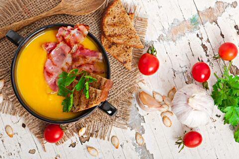 Klassiek pompoensoep recept feestelijk geserveerd met gebakken spek en korstjes