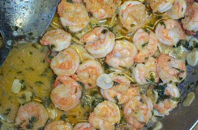 Bakken van scampi diabolique in boter en olijfolie met zeer fijngesneden groenten en knoflook
