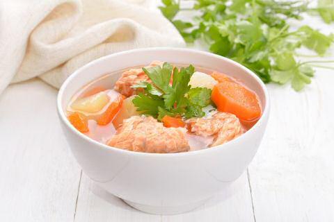 Een bord vissoep met stukken vis, veel garnalen, gegratineerd stokbrood en verse dille